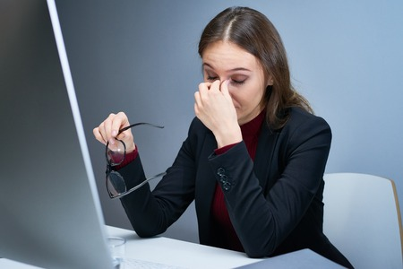 rubbing noses: Portrait of exhausted woman at office desk in front of computer screen taking glasses off and rubbing her nose bridge with eyes closed trying to calm headache and relieve stress. Stock Photo