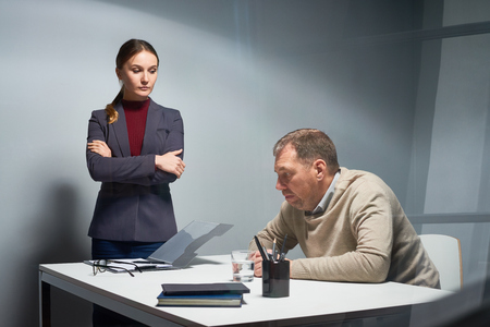 reprimand: Interrogation scene at police department: powerful female prosecutor with arms folded looking down at frustrated mature man suspected in crime, waiting for his answer. Shot from behind glass wall Stock Photo