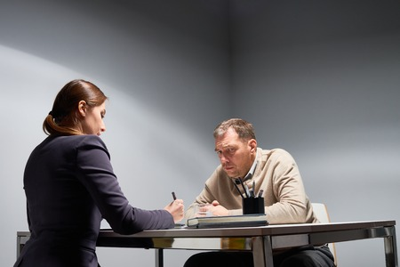 accusations: Unkempt middle-aged man facing angry lady boss at desk in empty gray interrogation room, looking guilty and sad while listening to accusations
