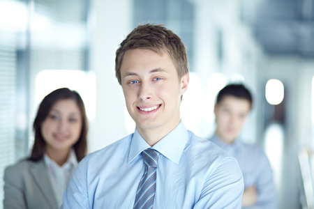 team from behind: Smiling businessman with his team behind him