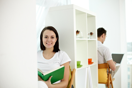 college dorm: Young girl reading sitting with a book and a man working with computer
