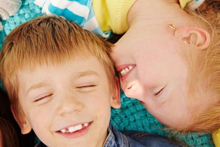 siblings: Directly above shot of happy little siblings lying on blanket