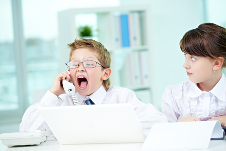 bossy: Little bossy boy shouting at telephone receiver and astonished girl looking at him