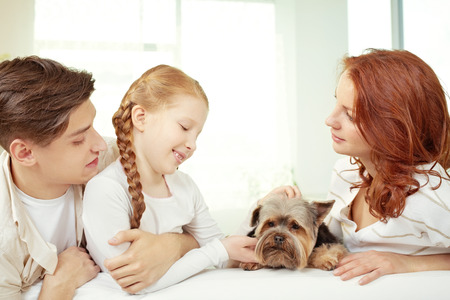 stroking: Portrait of little girl and her parents stroking a dog