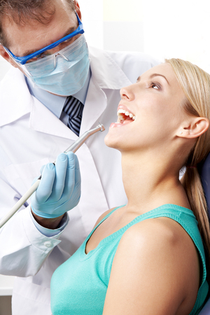 curing: Dentist curing teeth of young woman in clinic Stock Photo