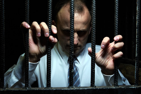 prison cell: Portrait of man in prison cell behind bars