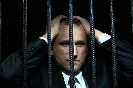 criminal: White collar criminal under arrest behind bars