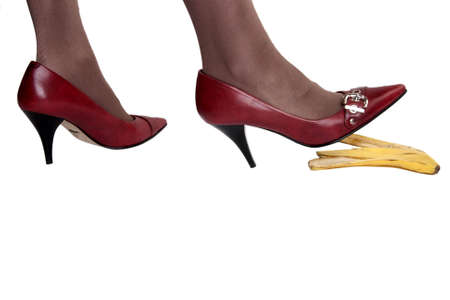 Feet in red pumps on banana peel ageinst a white background photo