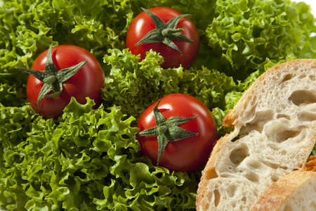 pices: Three tomatoes are in a lettuce with two pices of bread