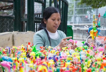 HANOI, VIETNAM - JAN 1, 2016: Female Vietnamese civilian artist (handicrafts man) making traditional toys (called To He) for children from special material of grain and colorful flour. Editorial