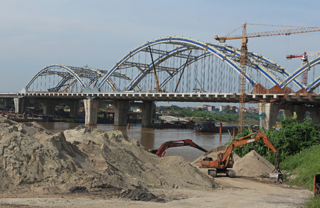 HANOI, VIETNAM - SEP 7, 2014: An under construction bridge connecting the two parts of Red river in Hanoi capital.