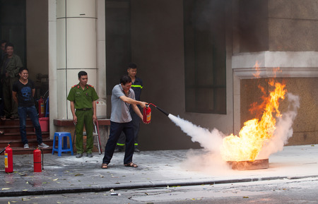 under fire: Hanoi, Vietnam - Nov 8, 2015: Asian civilian practicing to use fire extinguisher to rescue a fire in front of an office under the guide of professional fireman.