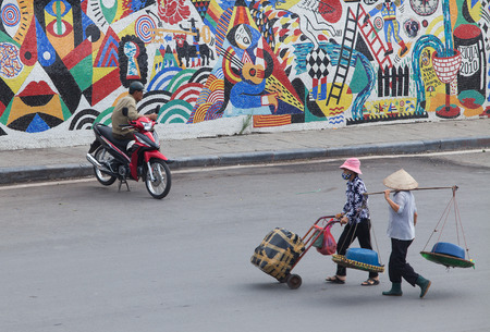 non la: Hanoi, Vietnam - Nov 10, 2015: A motorcycle driver (motor taxi) waiting for passenger on a street with a multi color wall behind and two women with conical hat carrying goods to the market in front.