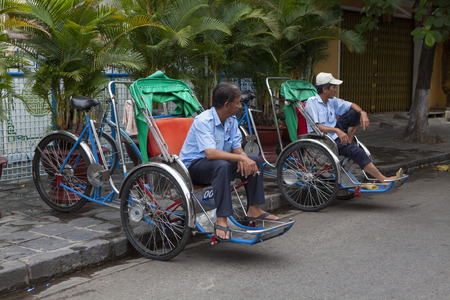 world cultural heritage: Hoi An, Vietnam - Jun 20, 2015: Cyclo drivers waiting for passenger on the side of a street in Hoi An ancient town. Hoi An is a world cultural heritage.