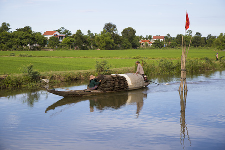 Hue, Vietnam - Jun 17, 2016: Vietnamese farmer with traditional conical hat driving a machine wooden boat on a canal providing water for the green paddy field.