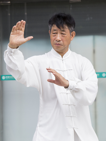 practised: Shenzhen, China - Jun 13, 2016: Chinese master practice Tai Chi on the side walk of a street. It is an internal Chinese martial art practised for both its defense training and its health benefits.