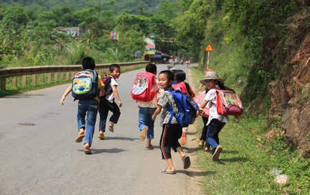 Hoa Binh, Vietnam - May 6, 2015: Young Vietnamese pupils walking home on a country road of Luong Son district after school. It's dangerous for children to join the traffic after school in Vietnam. Imagens - 64740563