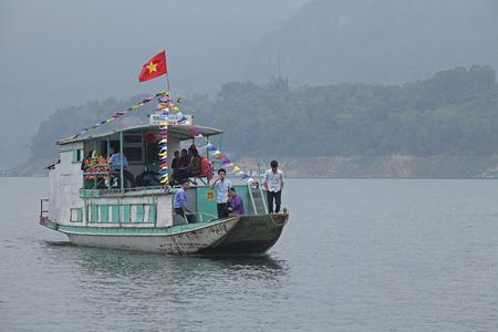 HOA BINH, VIETNAM - MAR 4, 2014: Passenger boat sailing on the lake of Hoa Binh Hydroelectricity Plant. Hoa Binh lake is the largest man made fresh water lake in Vietnam.