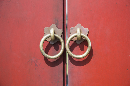 Ancient wooden gate with two door knocker rings close-up Stock Photo