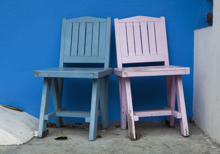 Two colorful chairs on blue wall