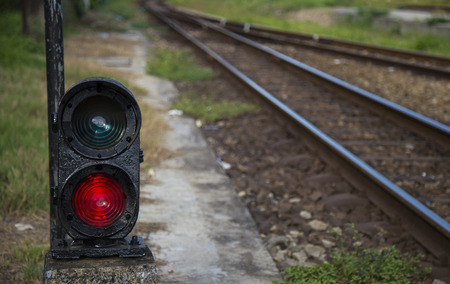 Railway traffic light at sunset shows red signal on railway. Stock Photo
