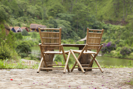 garden lawn: Close up of two bamboo chairs, view over a green valley of Da Lat city, Vietnam