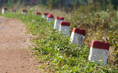 Red and white painted milestones in range on a country road under the sunlight Stock Photo