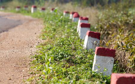 햇빛 아래 나라 도로에서 범위에서 빨간색과 흰색 페인트 이정표