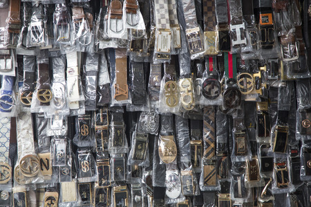 Hanoi, Vietnam - Nov 26, 2016: Close up of many made in China fashion leather belt with fake model of most well known luxury brands for whole sale and retail at Hang Dao old quarter street.