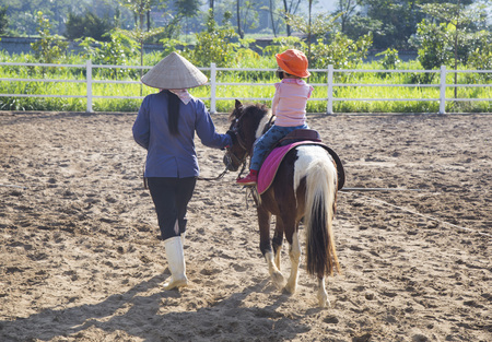Save Download Preview Asian baby girl riding horse with help from a trainer