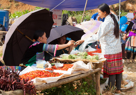 cau: LAO CAI, VIETNAM - OCT 17, 2015: Hmong tribe people selling chili pepper and other agriculture products at Can Cau flea market. Flea market is very popular as one kind of small business in Vietnam.