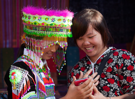 Lao Cai, Vietnam - Oct 17, 2015: Vietnamese Hmong minority girl trying new traditional costume and a colorful traditional hat at a weekly flea market in Bac Ha town.