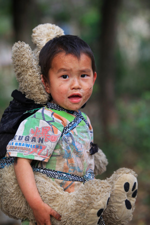ha giang: HA GIANG, VIETNAM - FEB 8, 2014: Unidentified Hmong child holding a teddy bear on back on a playground of his village. Editorial