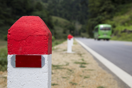 Red and white painted milestones in range on a country road under the sunlight. Concept of purpose and target, long term and the way to achieve success.
