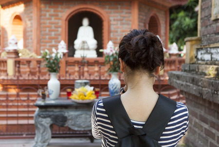 Young Vietnamese girl comes to Tran Quoc pagoda to pray for peace and happiness. This is the oldest Buddhist temple in Hanoi, Vietnam. Stock Photo