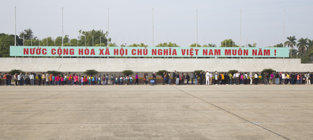 matching: Hanoi, Vietnam - Dec 17, 2016: Vietnamese people matching in line to visit Ho Chi Minh mausoleum at historic Ba Dinh square. This is a large memorial of the late communist president.