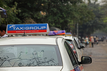 taxicabs: Hanoi, Vietnam - Mar 15, 2015: Taxi-cabs parking on the side of a street in Hanoi capital, Vietnam. Traffic is one of the most serious matter in the country with many vehicles on narrow streets. Editorial