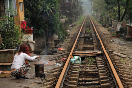 cramped: Hanoi, Vietnam - Mar 15, 2015: Usual life, transportation and houses on the railway track. Its dangerous to live here but poor people dont have many choices.