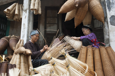to maintain: Hung Yen, Vietnam - Jul 26, 2015: Vietnamese craftsmen making bamboo handicraft products to maintain a traditional handicraft in a countryside of Vietnam.