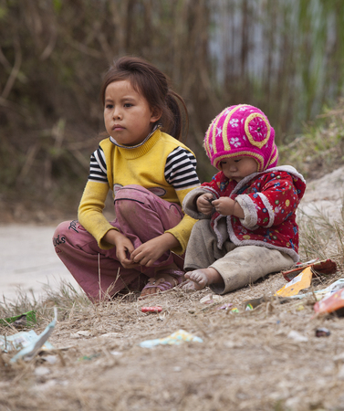 HA GIANG, VIETNAM - NOV 14, 2014: Close up photo of unidentified Hmong child eating candy on the ground in Dong Van rocky plateau. Dong Van rocky plateau is a well known geopark.