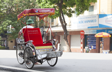 HANOI, VIETNAM - JUL 12, 2014: Life in Vietnam - cyclo driver waiting for customers in Sword lake. Cyclo is one of the most favorite vehicles for tourist when come to Vietnams cities.