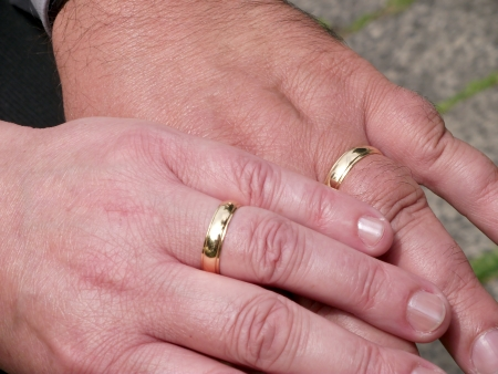 alliances: Two Hands with Wedding Rings