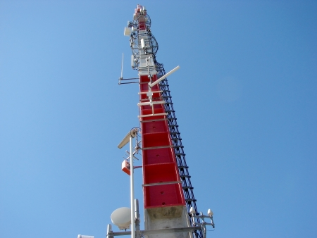 issuer: Top of a column of telecom against background of blue sky Stock Photo
