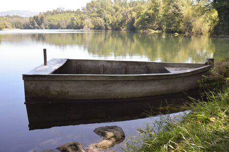 Old wooden boat anchored at the bank of a calm river on a summer day
