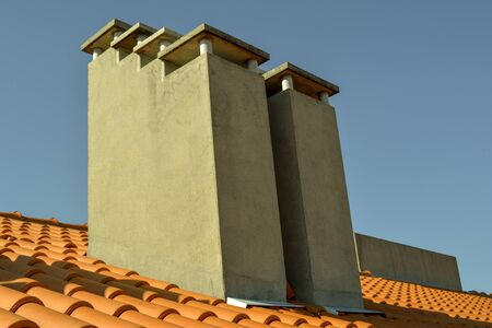 Set of concrete chimneys on a roof under a clear blue sky day