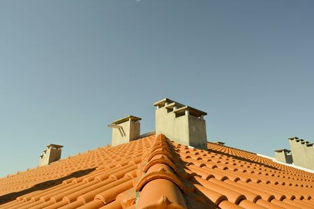 Detail of tiles and chimneys against a clear blue sky
