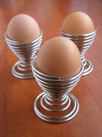 three metal spiral eggcup and three eggs