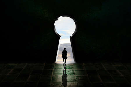 youngman walking alone in front of a big keyhole. light doorway Concept