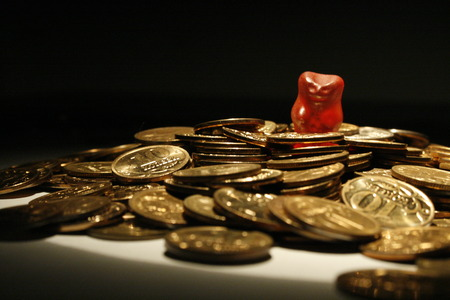 gummy bear: Red gummy bear in a pile of coins