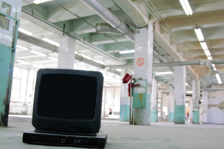 cast off: Old small black TV on the background of an empty office